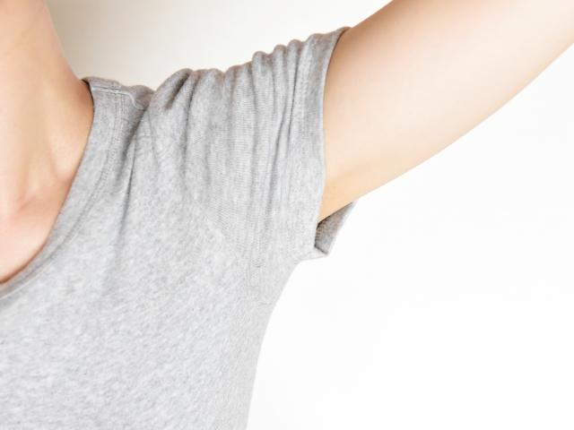 腕を上げたグレーのTシャツの女性